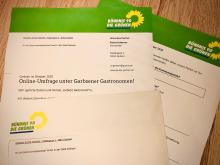 Foto zeigt auf Papier ausgedruckten Fragebogen mit Briefumschlag